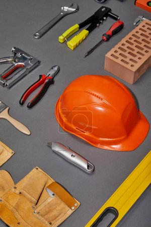 Photo for Flat lay with orange helmet, tool belt, brick, industrial tools and brush on grey background - Royalty Free Image