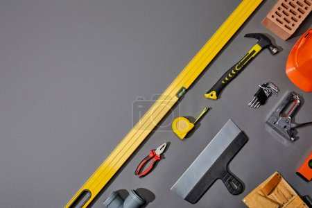 Photo for Flat lay with brick, hammer, measuring tape, helmet, tool belt and industrial tools on grey background - Royalty Free Image