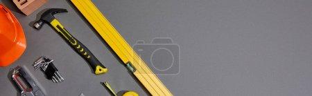 Photo for Panoramic shot of spirit level, hammer, angle keys, work helmet, stapler and measuring tape on grey background - Royalty Free Image