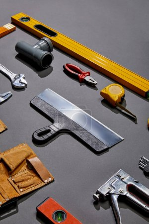 Photo for High angle view of putty knife, spirit levels, pipe connector, pliers, measuring tape, monkey wrench, tool belt and stapler on grey background - Royalty Free Image
