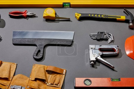 Photo for High angle view of spirit levels, pliers, measuring tape, hammer, putty knife, angle keys, stapler and tool belt on grey background - Royalty Free Image