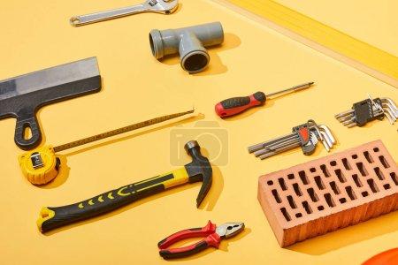 Photo pour Planche à plat avec marteau, raccord de tuyau, clé d'angle, tournevis, pinces, brique, ruban à mesurer et couteau masqué sur fond jaune - image libre de droit