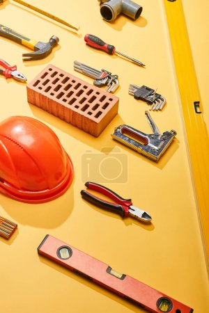 Photo pour Pose plate avec outils industriels, brique et casque sur fond jaune - image libre de droit