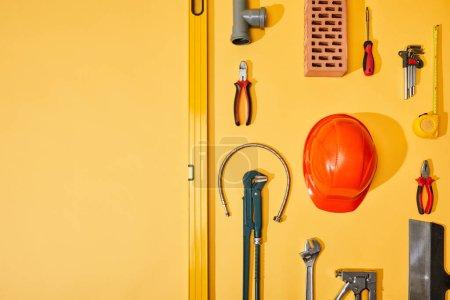 Photo pour Pose plate avec outils industriels, ruban à mesurer et casque, sur fond jaune - image libre de droit