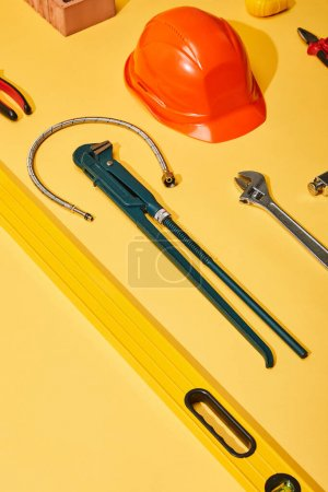high angle view of calipers, helmet, monkey wrench, spirit level, brick, pliers and plumbing hose on yellow background