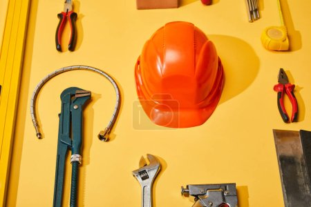 Photo for Flat lay with helmet, calipers, monkey wrench, putty knife, plumbing hose, spirit level, measuring tape and angle keys on yellow background - Royalty Free Image