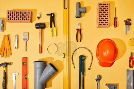 Photo pour Pose plate avec outils industriels, briques et casque sur fond jaune - image libre de droit