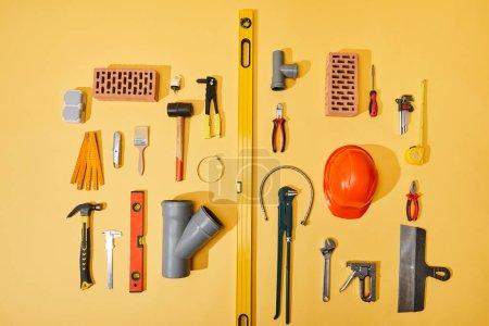 Photo pour Vue de dessus des briques, des outils industriels, du casque, du tuyau de plomberie et du ruban à mesurer sur fond jaune - image libre de droit