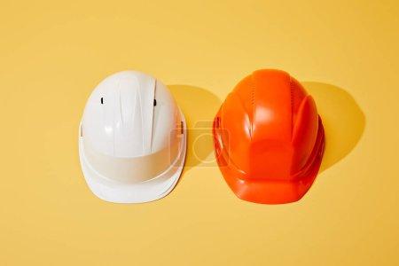 Photo pour Vue de dessus des casques orange et blanc sur fond jaune - image libre de droit