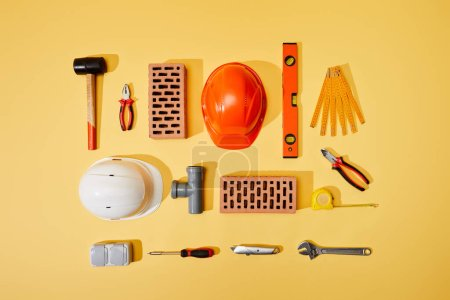 Photo for Top view of bricks, helmets, measuring tape, and industrial tools on yellow background - Royalty Free Image