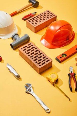 Photo for High angle view of bricks, helmets, and industrial tools on yellow background - Royalty Free Image