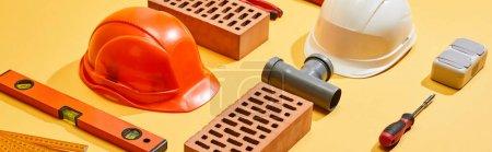 Photo pour Plan panoramique de briques, casques, niveau d'alcool, connecteur de tuyau, règle pliante et tournevis sur fond jaune - image libre de droit