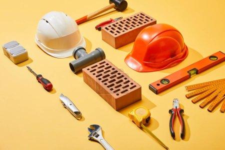 Photo pour Vue grand angle des outils industriels, des briques et des casques sur fond jaune - image libre de droit