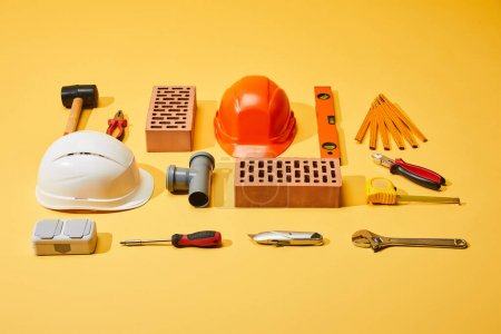 Photo for Flat lay with bricks, helmets, industrial tools and measuring tape on yellow background - Royalty Free Image