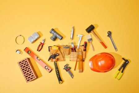 Photo pour Vue aérienne de la ceinture à outils, de la brique, des outils industriels et du casque sur fond jaune - image libre de droit
