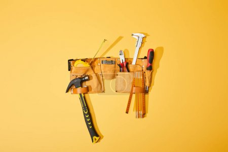 Photo for Top view of tool belt with hammer, pliers, measuring tape, calipers, screwdriver and folding ruler on yellow background - Royalty Free Image