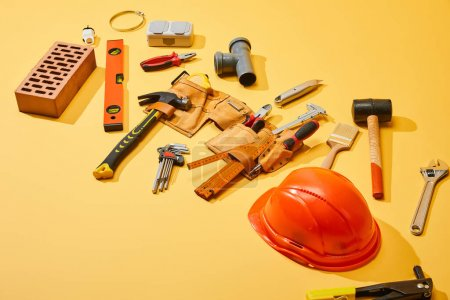 Photo pour Vue grand angle de la ceinture d'outils avec outils industriels, brique et casque sur fond jaune - image libre de droit