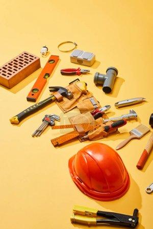 Photo pour Vue à angle élevé de la ceinture de sécurité, des outils industriels, de la brique et du casque sur fond jaune - image libre de droit