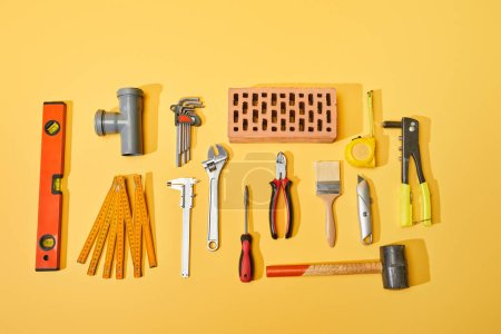 Photo for Top view of industrial tools and brick on yellow background - Royalty Free Image