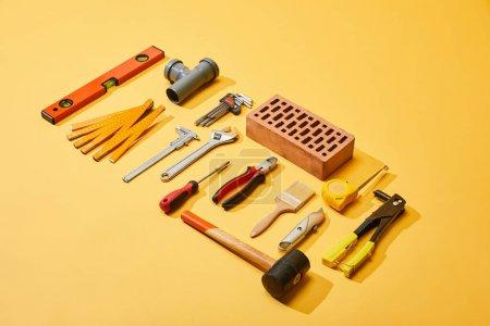 Photo pour Vue à angle élevé des outils industriels et brique sur fond jaune - image libre de droit