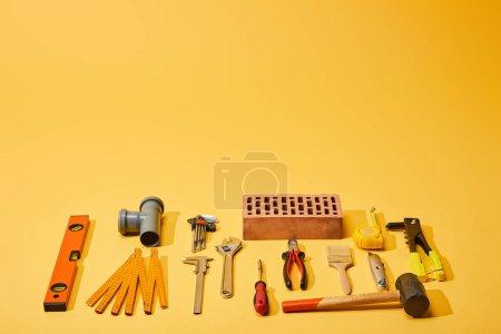 Photo pour À plat avec outils industriels et brique sur fond jaune - image libre de droit