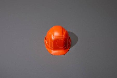 Blick auf den orangefarbenen Helm auf grauem Hintergrund
