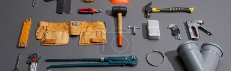 Foto de Foto panorámica de herramientas industriales y correa de herramientas sobre fondo gris - Imagen libre de derechos