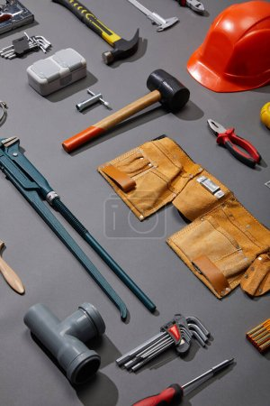 Photo for High angle view of tool belt, hammers, monkey wrench, putty knife, pliers, helmet, pipe connector, calipers, angle keys and brush on grey background - Royalty Free Image