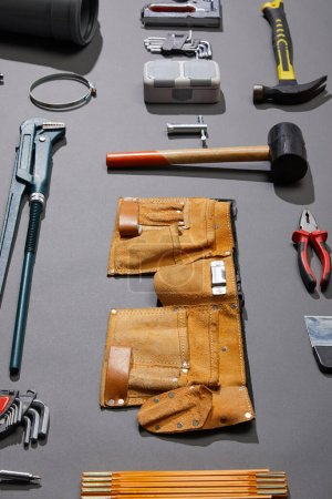 Photo pour Vue à angle élevé de la ceinture à outils, des marteaux, de la clé à singe, du couteau, des pinces, des compas, du canon à rivet, des clés à angle et de l'agrafeuse sur fond gris - image libre de droit
