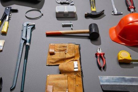 Photo pour Vue à angle élevé de la ceinture à outils, du casque, des marteaux, de la clé à singe, du couteau, des pinces, des compas, du canon à rivet et du ruban à mesurer sur fond gris - image libre de droit