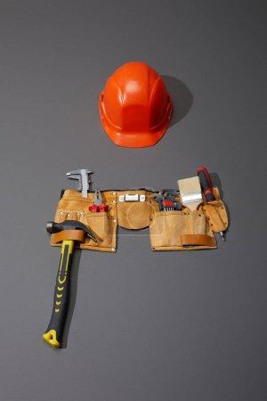 Photo pour Vue grand angle du casque, ceinture à outils avec marteau, brosse, pinces, étriers, clés d'angle et tournevis sur fond gris - image libre de droit