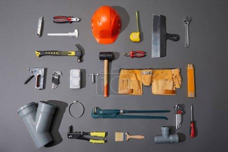 płaski układ narzędzi przemysłowych, kasku, taśmy pomiarowej, paska narzędziowego i szczotki na szarym tle