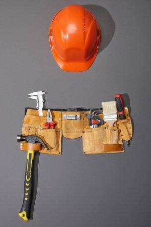 Photo pour Vue du dessus du casque, de la ceinture à outils avec marteau, brosse, pinces, étriers, clés d'angle et tournevis sur fond gris - image libre de droit