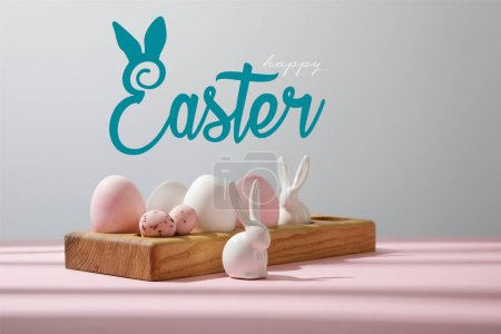 Photo pour Easter eggs on wooden board with decorative rabbits on pink and grey with happy Easter illustration - image libre de droit