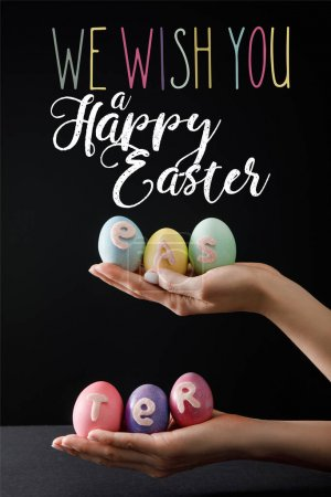 Photo pour Selective focus of Easter eggs on wooden board on black with we wish you a happy Easter illustration - image libre de droit