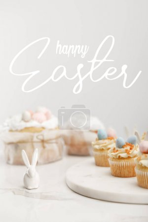 Photo pour Selective focus of cupcakes on round board, decorative bunny and easter cakes on grey background with happy Easter illustration - image libre de droit
