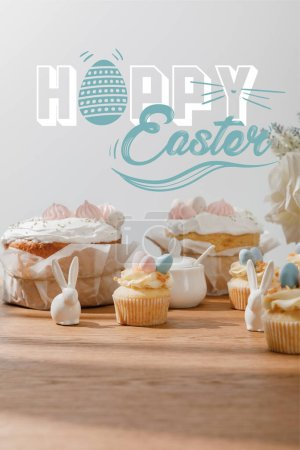 Photo pour Selective focus of cupcakes with decorative bunnies, sugar bowl, easter cakes and flowers isolated on grey with happy Easter illustration - image libre de droit
