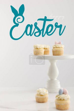 Photo pour Selective focus of cupcakes on cake stand isolated on grey with happy Easter illustration - image libre de droit