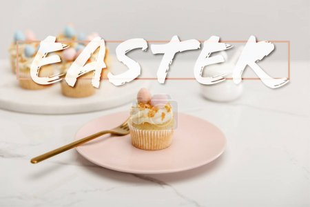 Photo pour Selective focus of cupcakes on plate with fork and round board with sugar bowl on grey background with Easter illustration - image libre de droit