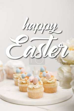 Photo pour Selective focus of cupcakes on round board with flowers on grey background with happy Easter illustration - image libre de droit