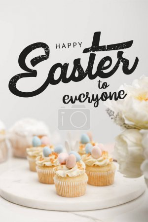 Photo pour Selective focus of cupcakes on round board with flowers on grey background with happy Easter to everyone illustration - image libre de droit