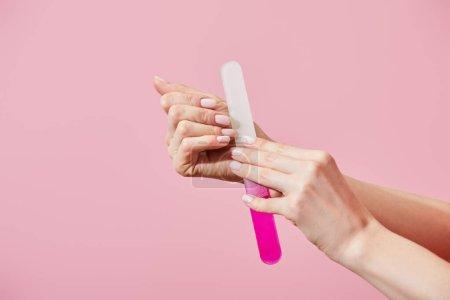 Photo pour Vue partielle d'une femme faisant de la manucure avec une lime à ongles isolée en rose - image libre de droit