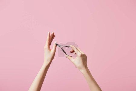 Photo pour Vue partielle d'une femme coupant la cuticule avec son mamelon isolé en rose - image libre de droit