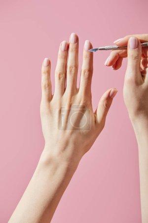 Photo pour Vue partielle d'une femme faisant de la manucure avec un pousseur de cuticule isolé en rose - image libre de droit
