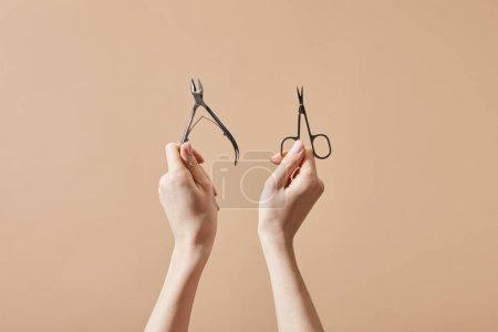 Photo pour Vue en croûte d'une femme tenant une tétine de cuticule et des ciseaux à ongles isolés sur du beige - image libre de droit