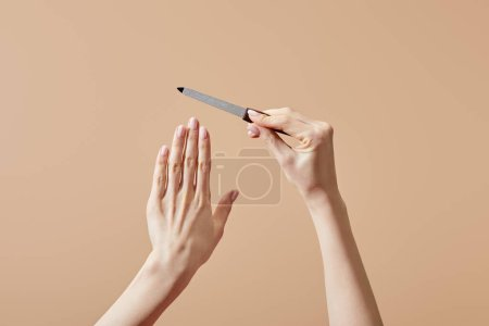 Photo for Cropped view of female hands with nail file isolated on beige - Royalty Free Image