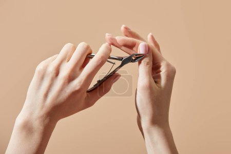 Photo for Cropped view of woman doing manicure with cuticle nipper isolated on beige - Royalty Free Image