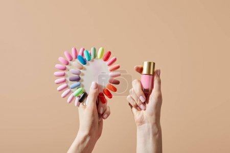 Photo pour Vue croustillante d'une femme tenant une bouteille et échantillons de vernis à ongles isolés sur beige - image libre de droit