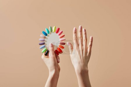 Foto de Vista parcial de la mujer que tiene muestras multicolores de pulido de uñas aislado sobre la colza. - Imagen libre de derechos
