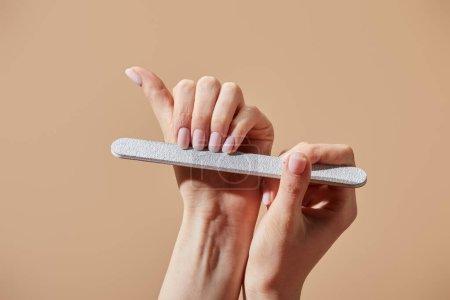 Photo pour Vue croustillante d'une femme déposant des ongles avec un carton d'émeri isolé sur un beige - image libre de droit